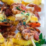 Close up view of cajun prawns and pineapple skewers