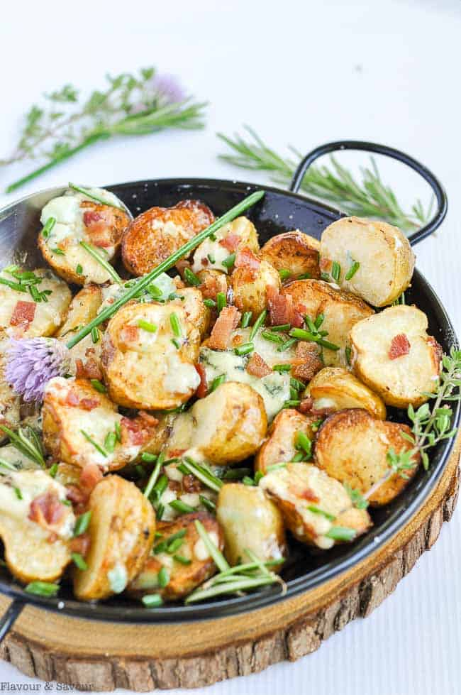 Crispy Grilled Potatoes with Blue Cheese in a skillet with rosemary