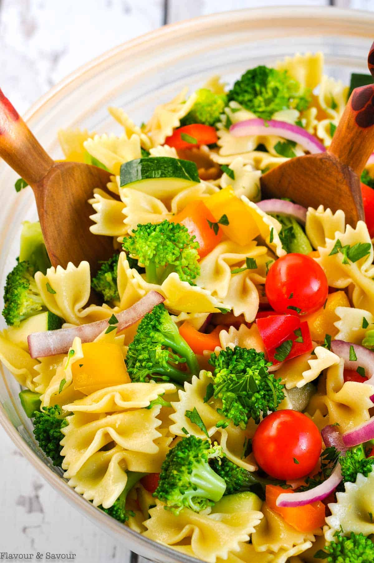 close up view of a bowl of pasta salad with servers