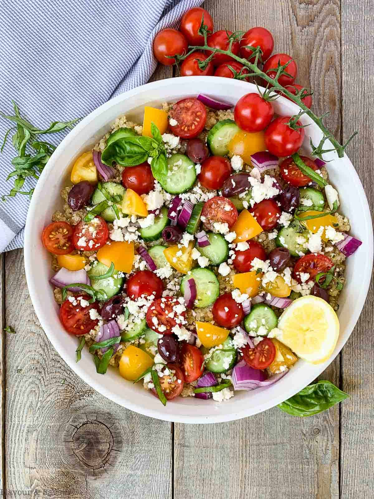 Mediterranean Quinoa Salad on a board with a sprig of cherry tomatoes