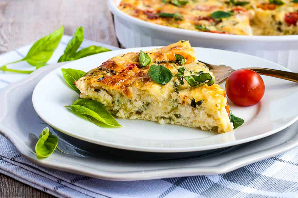 A slice of Cheesy Crustless Zucchini Quiche on a plate with basil and tomatoes