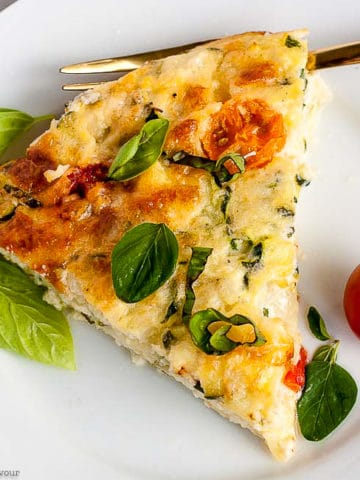 A slice of Cheesy Crustless Zucchini Quiche on a plate with basil leaves