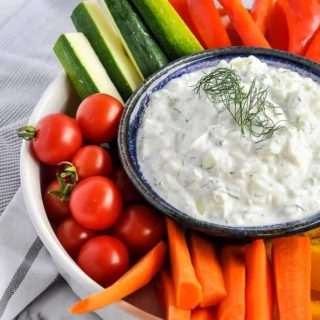 Authentic Tzatziki Dip in a bowl surrounded by fresh vegetables