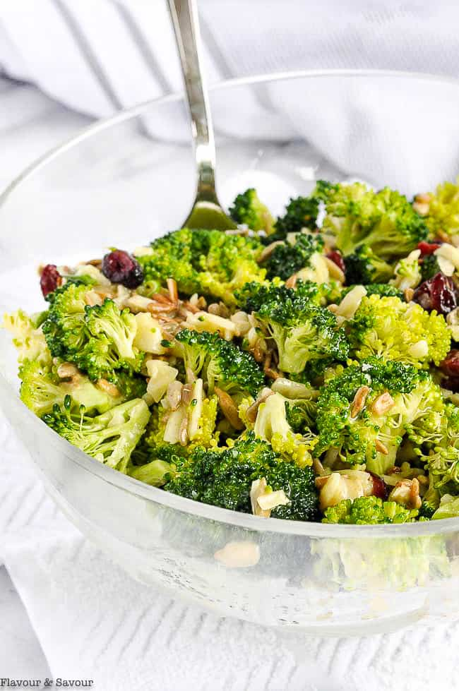 Broccoli Salad with cranberries in a glass bowl with a serving spoon