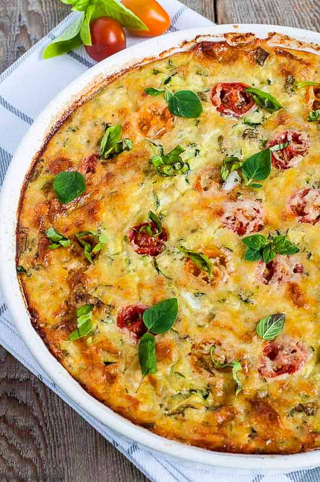 Close up view of Cheesy Crustless Zucchini Quiche in a round white quiche dish