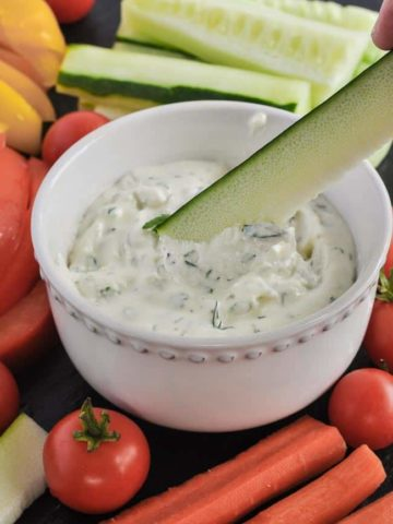 Dipping zucchini stick into Herbed Feta Dip with Lemon