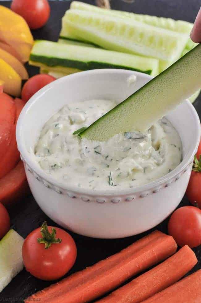 Dipping a zucchini stick into herbed feta dip