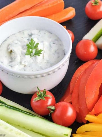 A bowl of dip surrounded by fresh vegetable sticks.