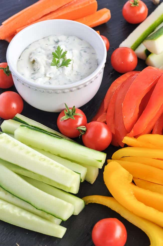 Herbed Feta Dip surrounded by fresh vegetable sticks.