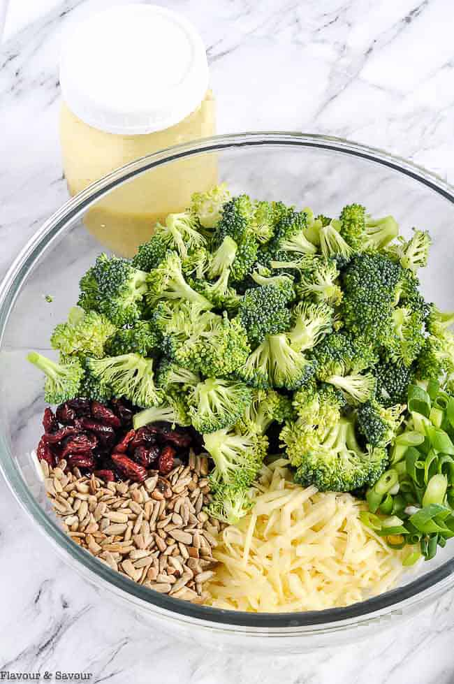 Ingredients for Broccoli Salad with Cranberries in a glass bowl with a jar of honey-dijon dressing