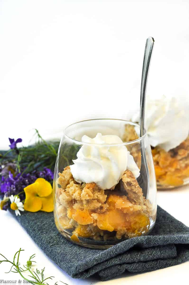 Peach Crisp with Bourbon and Vanilla in a dessert glass with a spoon