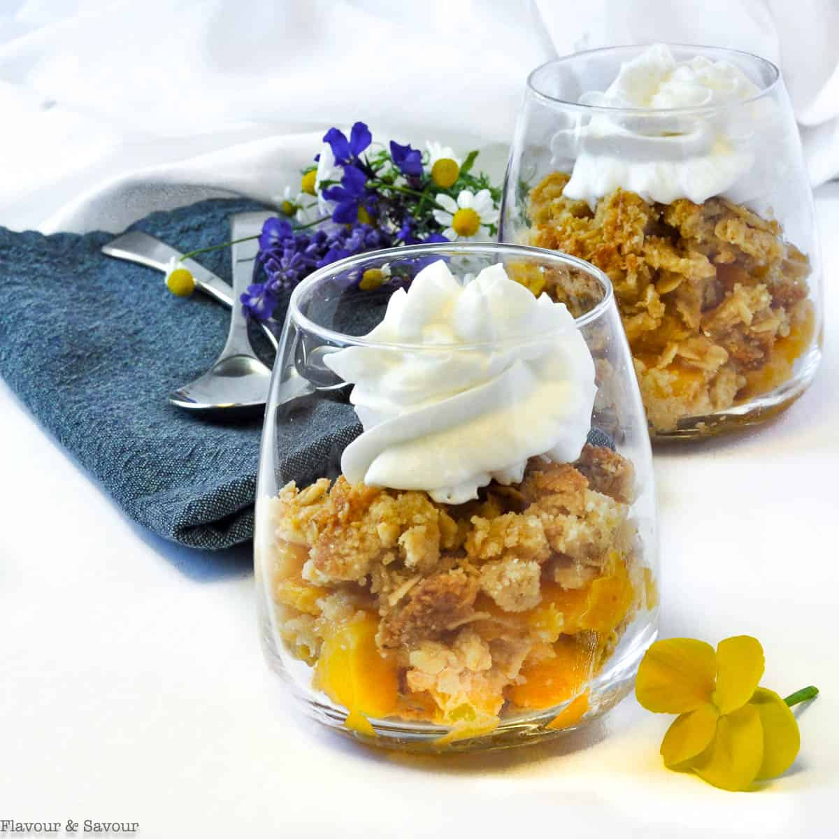 Two dessert glasses with Peach Crisp and whipped coconut milk