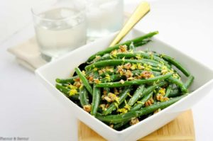 Parmesan Pecan Green Beans in a serving bowl with a gold spoon