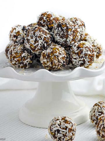 Chocolate Coconut Snowballs on a white pedestal cake plate