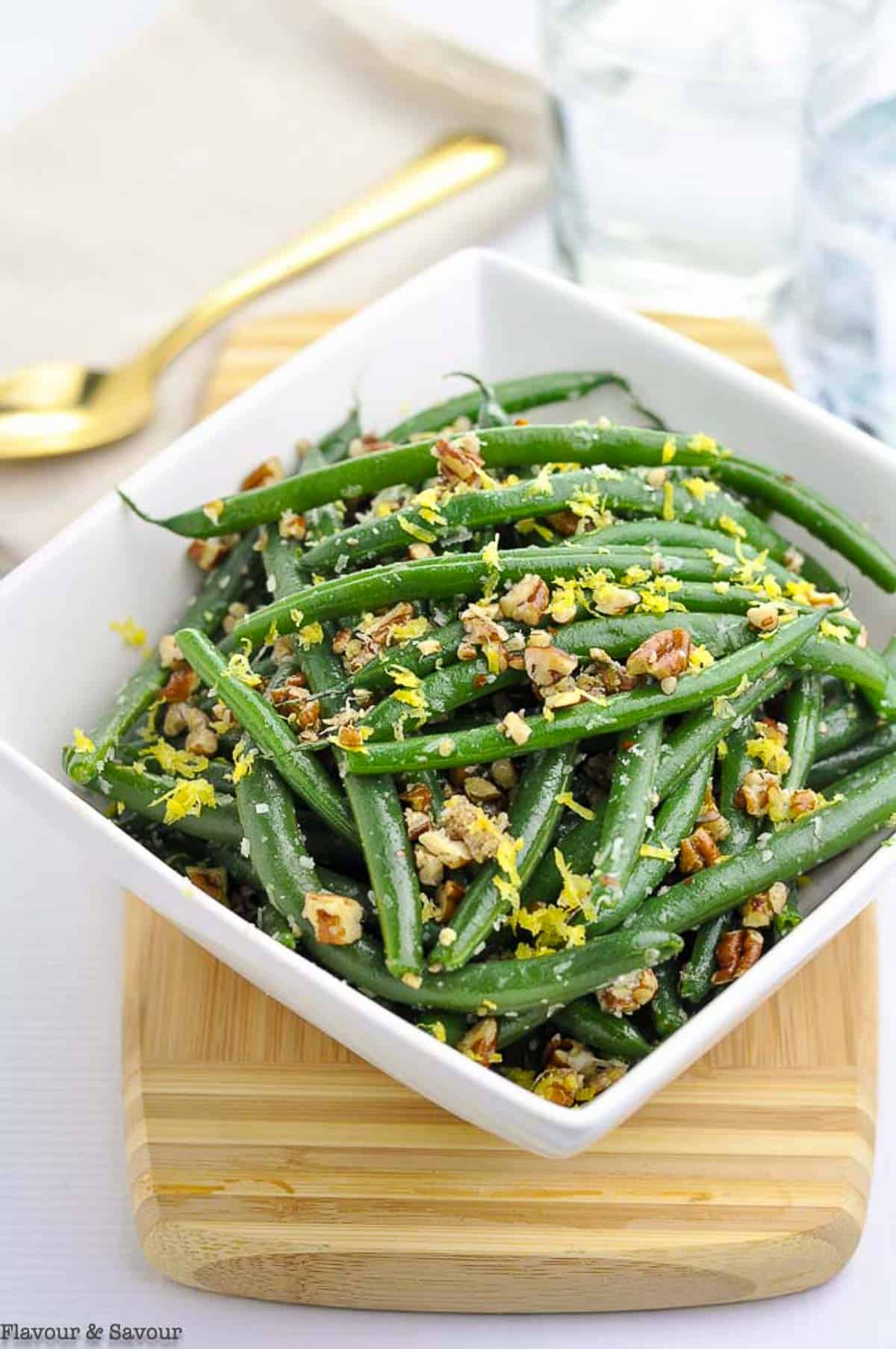 A square bowl of green beans garnished with pecans and Parmesan cheese.