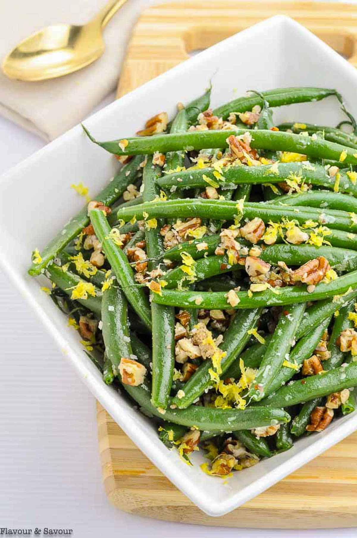 a bowl of green beans with parmesan cheese and pecans