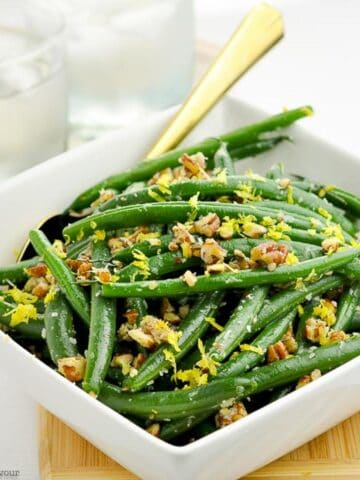 A bowl of Parmesan Green Beans with pecans in a square bowl with a spoon.