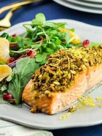 a pistachio-crusted fillet of salmon on a plate with a side salad