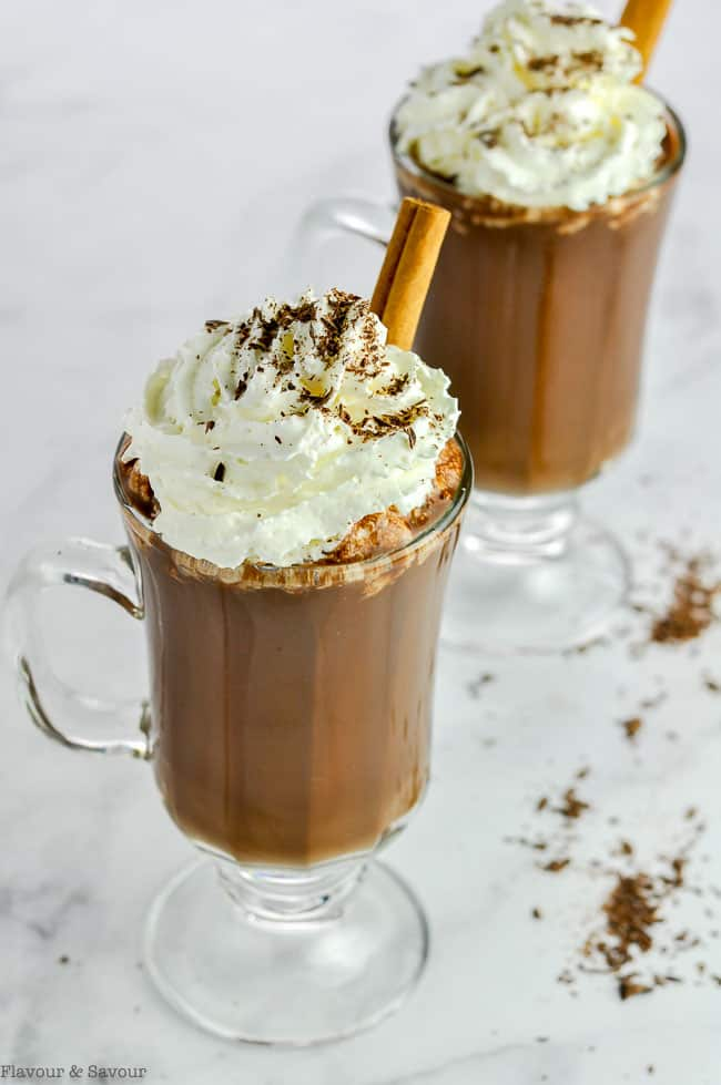 A mug of Cashew Milk Mexican Hot Chocolate, also called Spiced Hot Cocoa, with whipped cream and a cinnamon stick