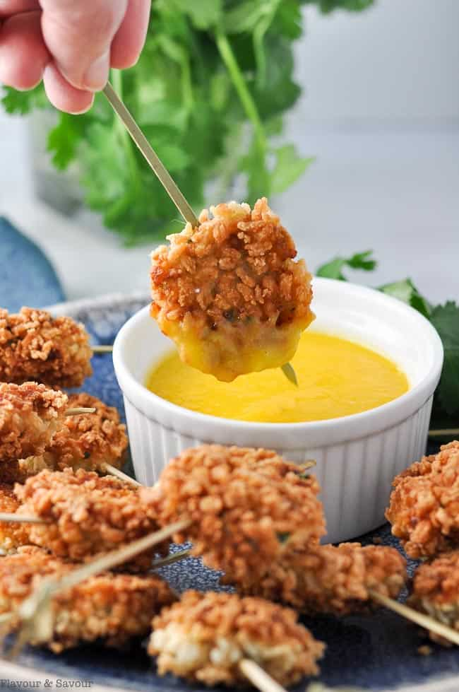 close up view of a skewered shrimp cake dunked in mango dip