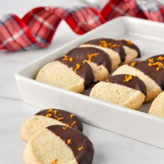 Orange Cardamom Almond Flour Cookies with plaid ribbon in background
