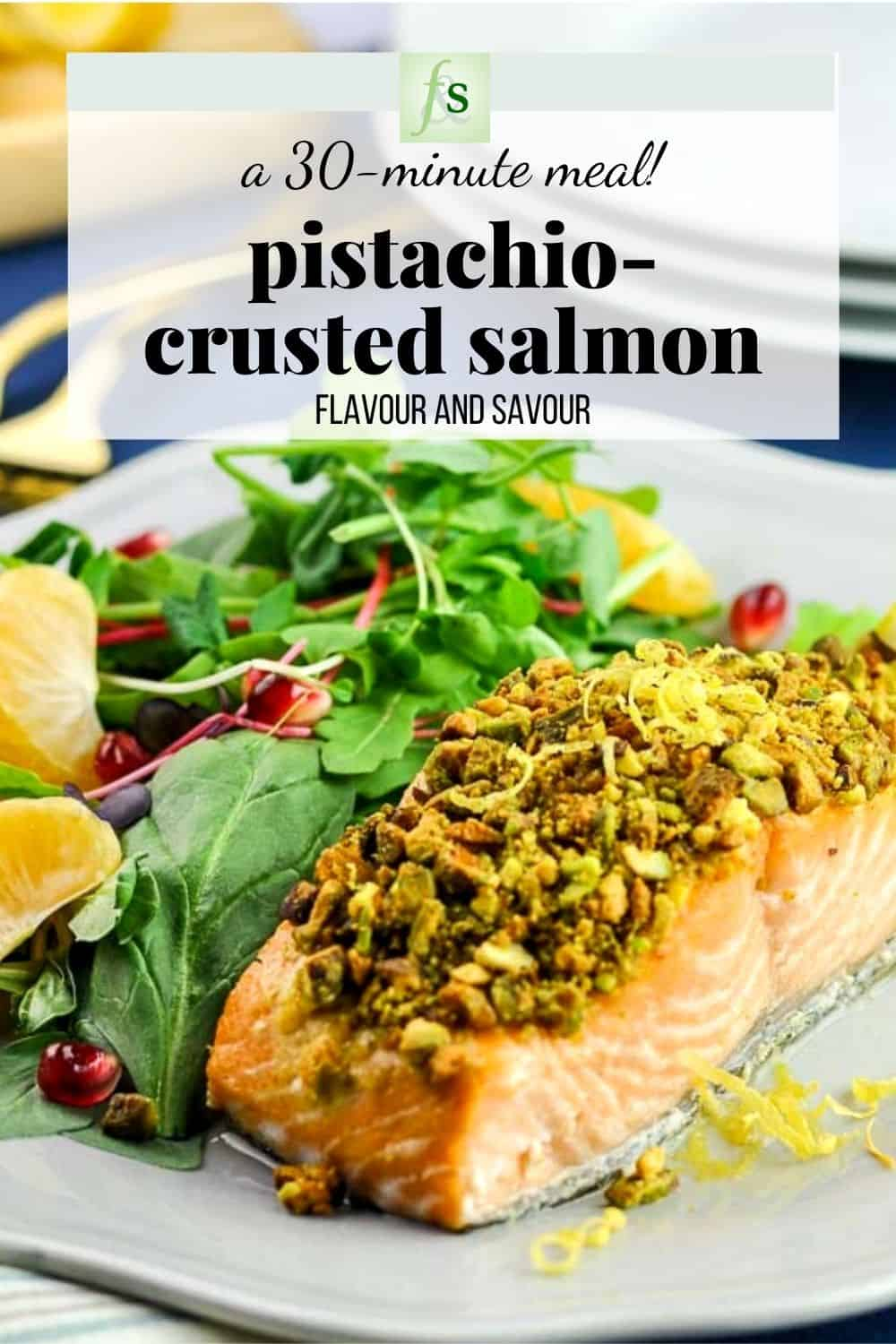a fillet of pistachio-crusted salmon aon a plate with a side salad