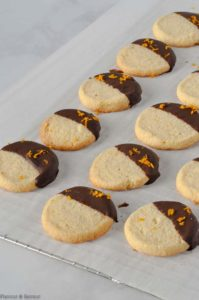 Chocolate Dipped Cardamom Orange Almond Cookies on a cooling rack