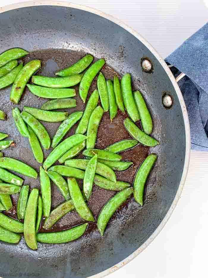 Sautéed snow peas in a skillet