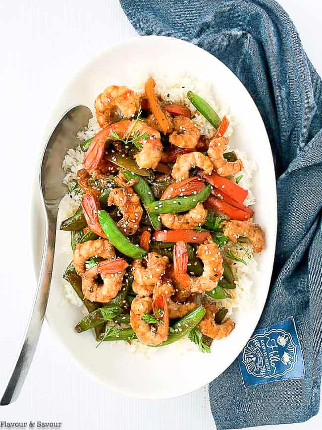 Overhead view of Shrimp and Snow Pea Stir Fry in a white bowl with a spoon