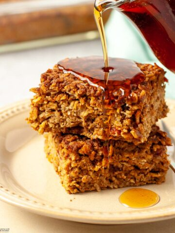 Two squares of pumpkin baked oatmeal with maple syrup