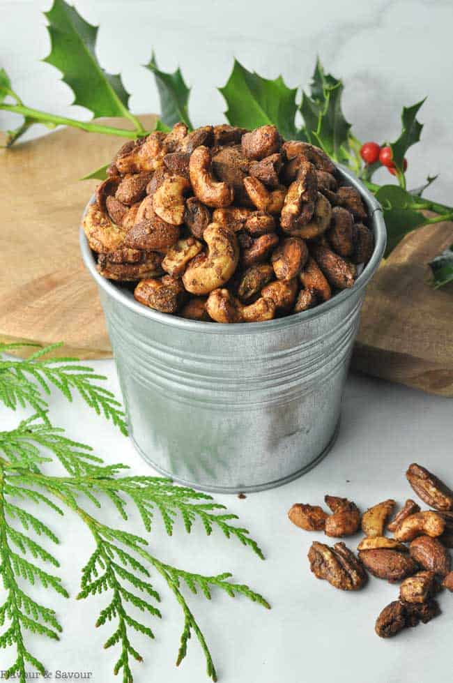 Gingerbread Spiced Nuts in a metal tin with cedar and holly