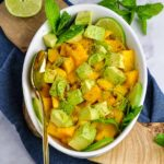 A white oval bowl with mango and avocado cubes