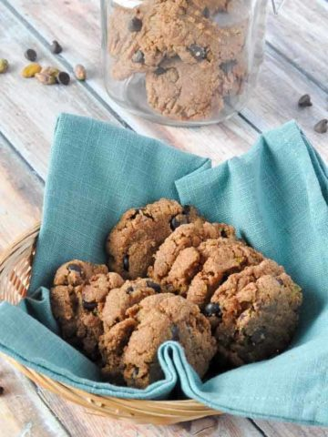 Almond Butter cookies in a basket with a cookie jar in the background.