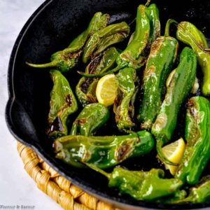Blistered Shishito Peppers in a cast-iron skillet with lemon slices