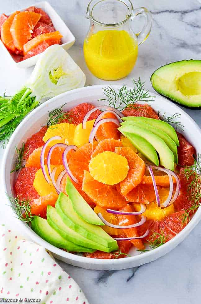 Overhead view of Grapefruit Orange Avocado Salad with a jar of dressing
