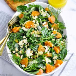 Overhead view of Kale and Cara Cara Orange Salad in a white oval bowl with dressing in the background.