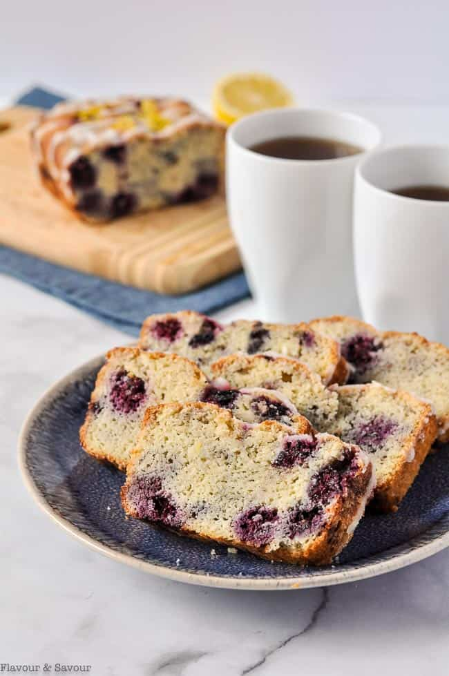 Slices of Sugar-free Blackberry Bread on a plate with two coffee cups.