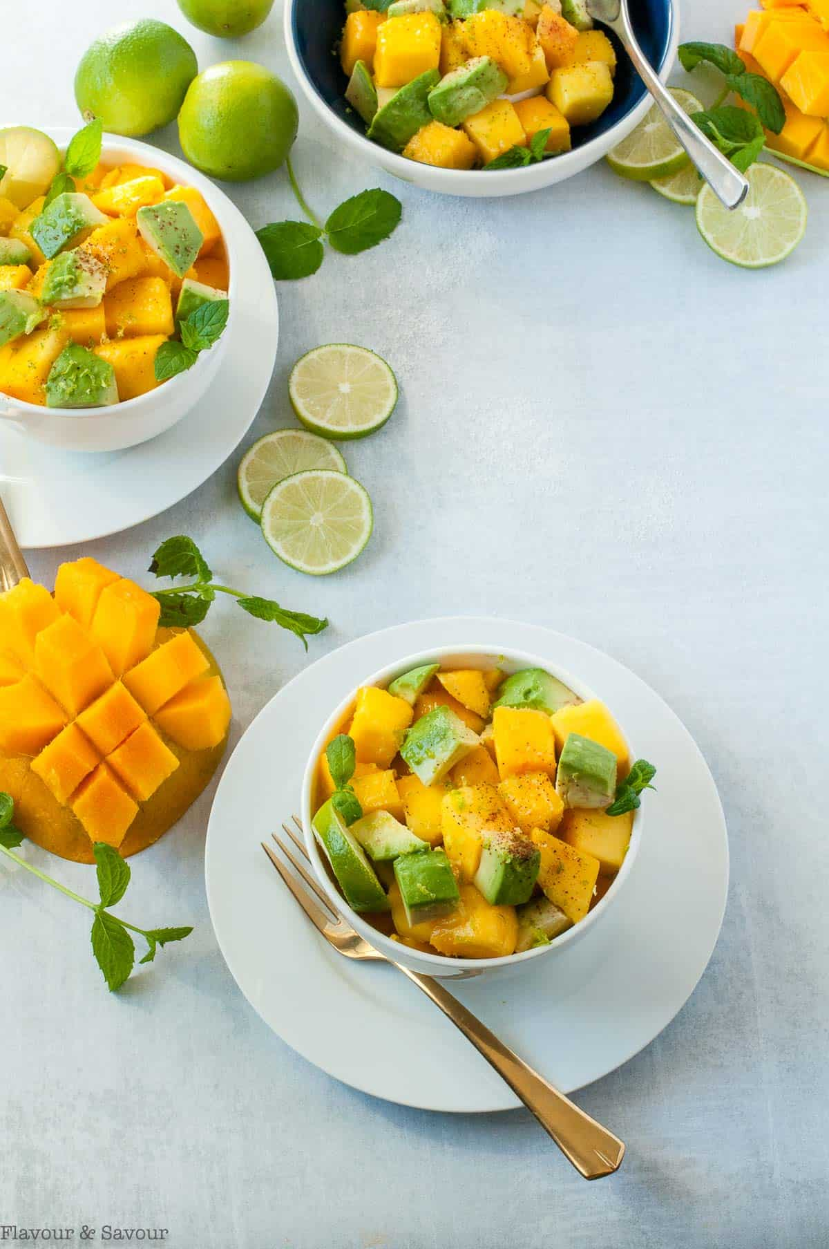 three bowls of Mango Avocado Chili Lime Salad with lime slices, mint leaves and cubed mango on the table