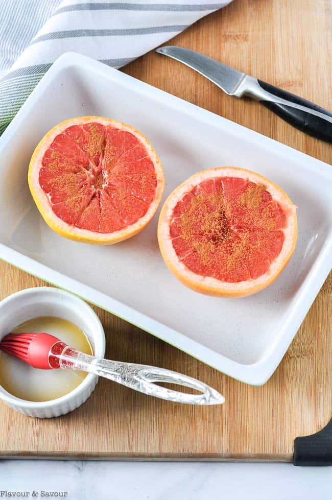 Two broiled grapefruit halves sprinkled with salt, cinnamon and maple syrup