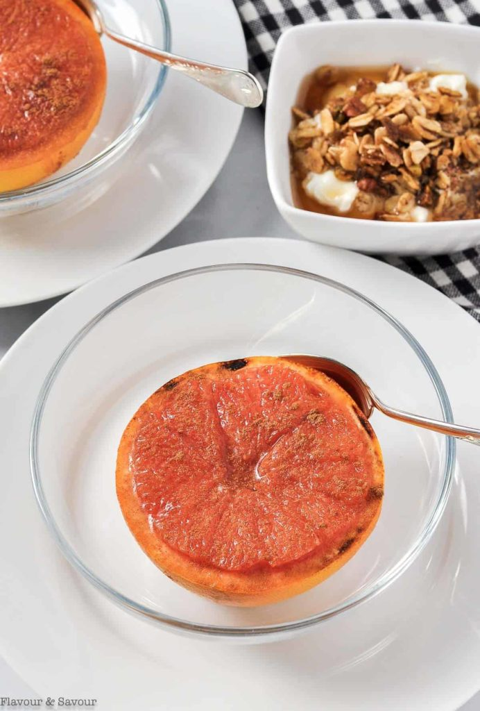 Two broiled grapefruit halves in glass bowls topped with maple syrup and cinnamon.