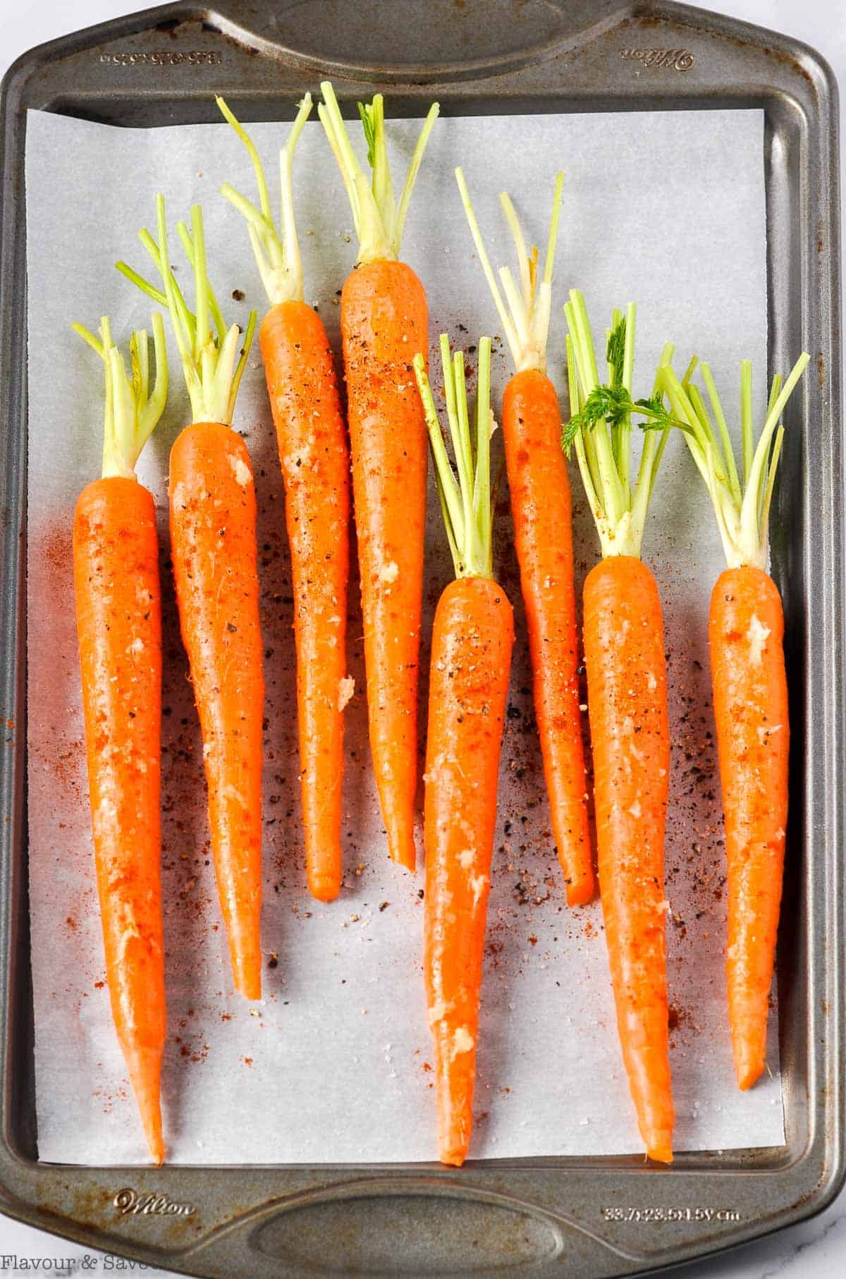 Whole carrots on a baking sheet ready to roast in the oven.