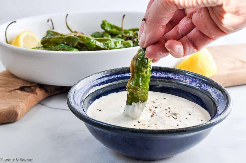 Dipping a Shishito or Padron pepper in lemon aioli