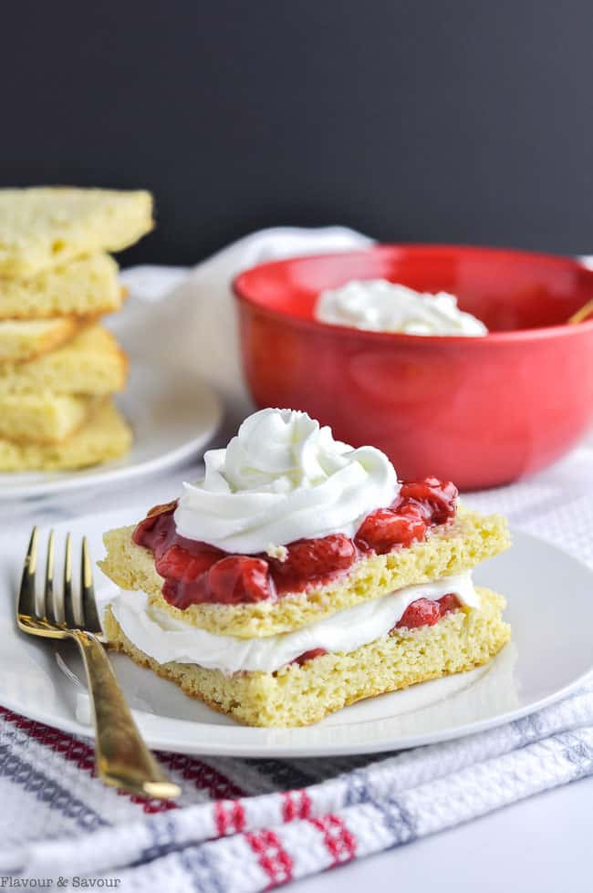 Strawberry Shortcake with a gold fork and a bowl of whipped cream in the background