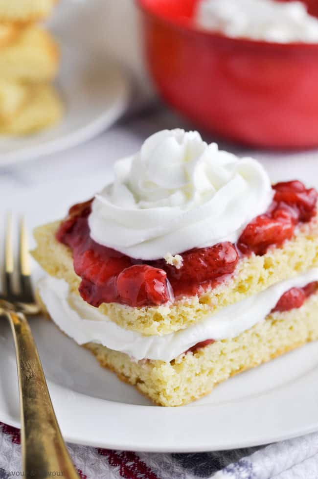 Close up view of Strawberry Shortcake with a red bowl in the background.