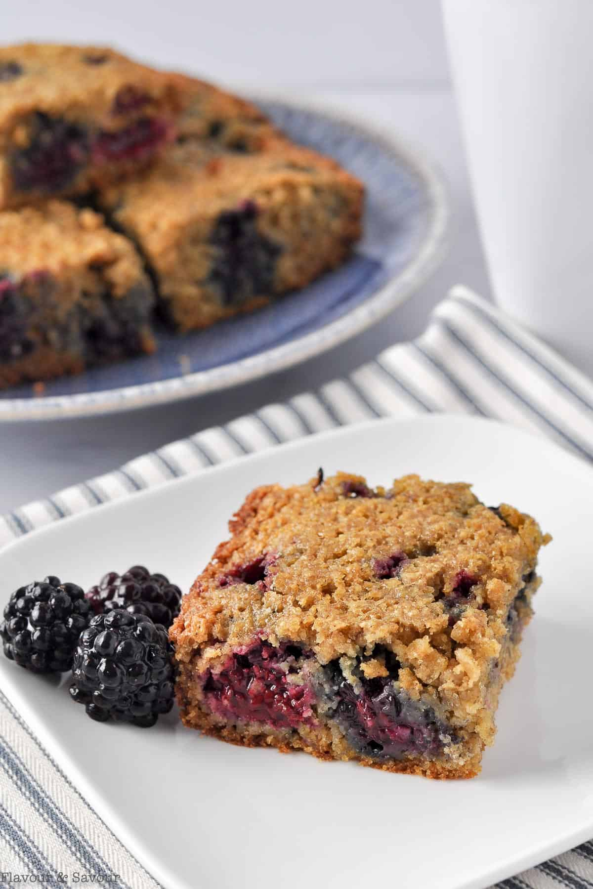 A blackberry oatmeal bar with fresh blackberries on a small square white plate