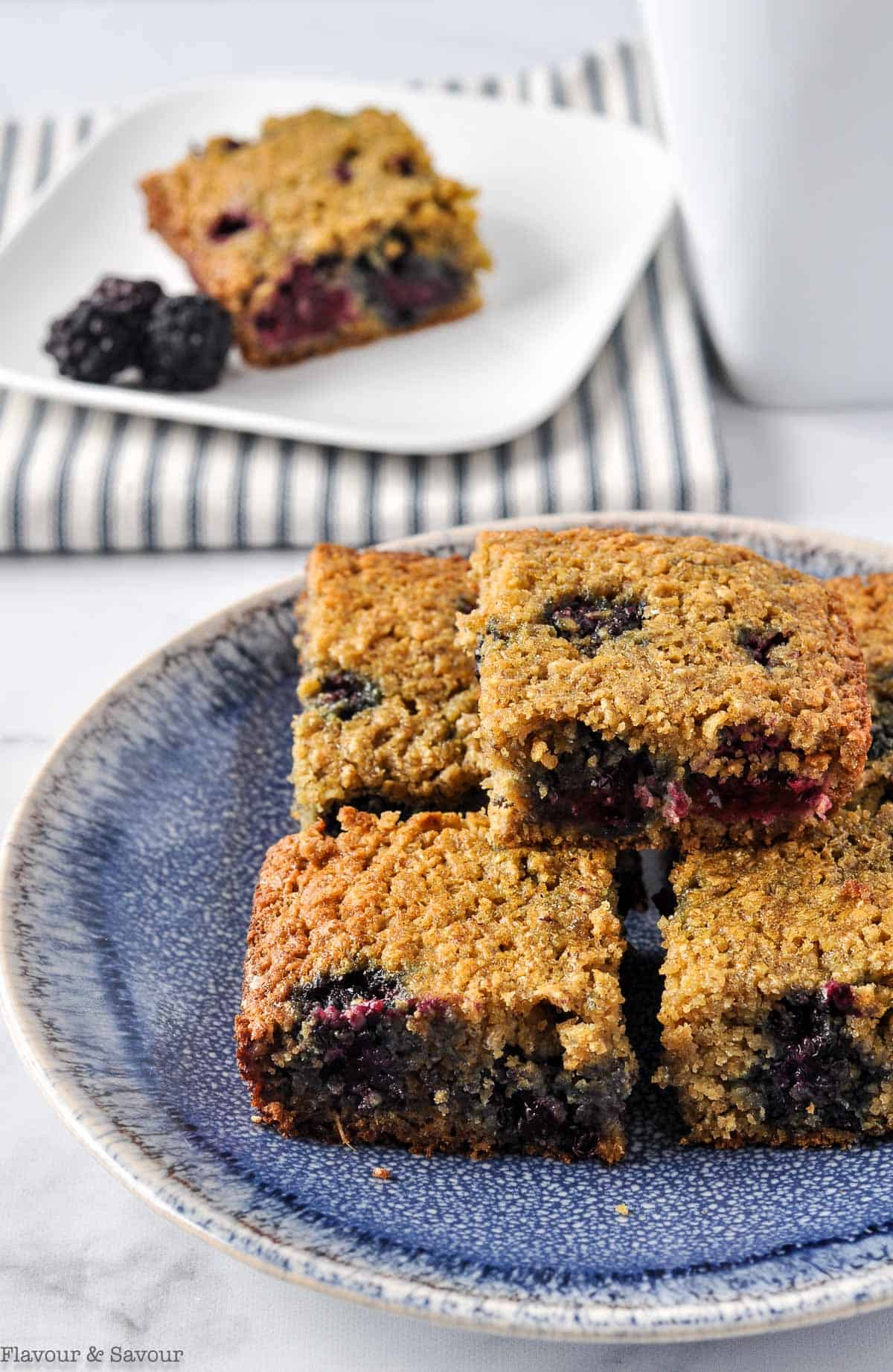 A stack of blackberry oatmeal breakfast bars on a blue stoneware plate.