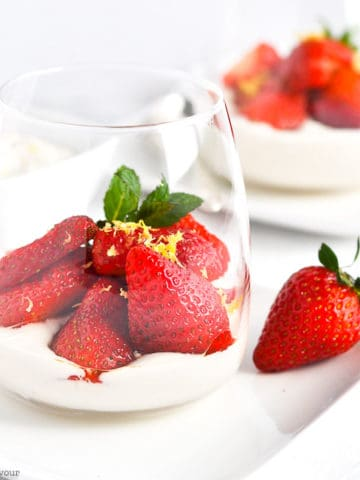 a dessert glass with cashew cream and macerated strawberries