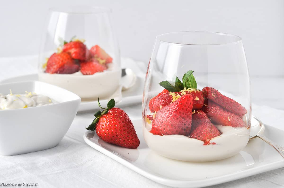 Macerated sliced strawberries in clear dessert glasses with a small bowl of cashew cream beside.