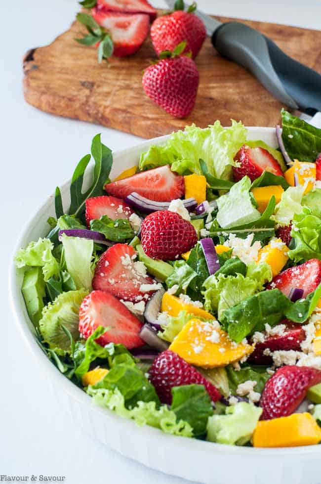 Strawberry Mango Arugula Salad with wooden salad servers