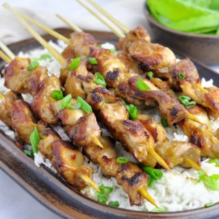 Thai Chicken Skewers on Coconut Rice on a brown stoneware platter